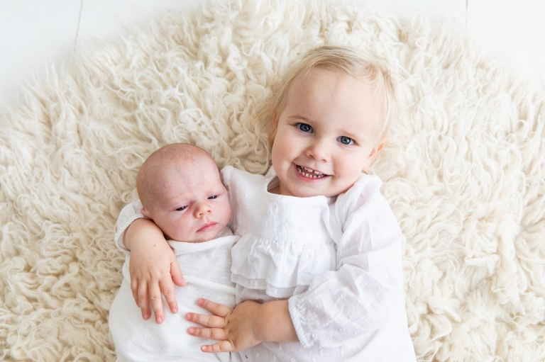 Big sister holds her new baby sister