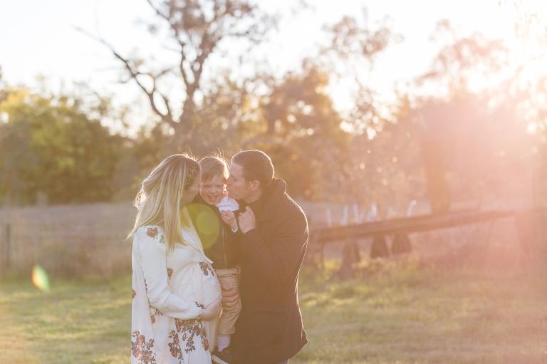 Mum and dad kiss their little boy