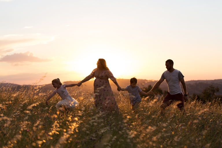 Family walks across the hill at sunset