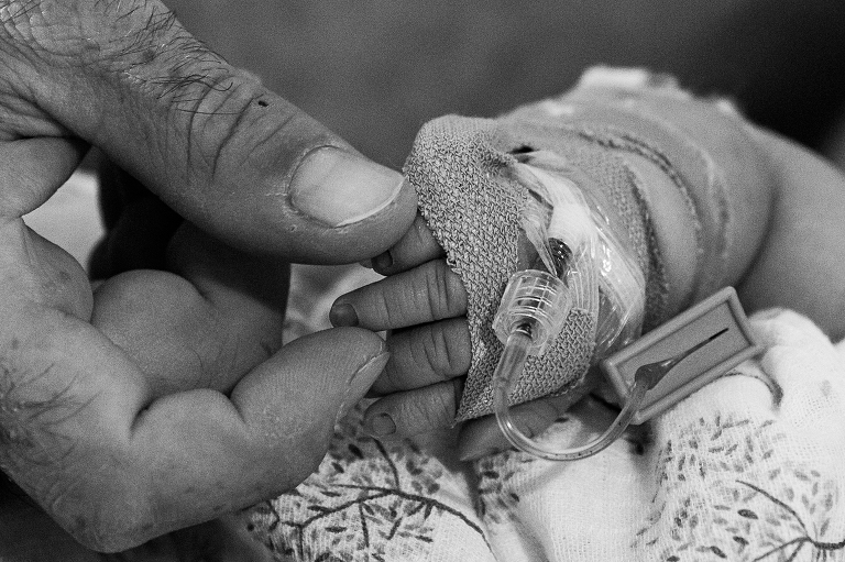 Dad holds his newborn baby's fingers
